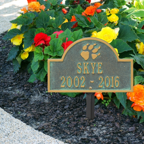 Bronze Verdigris Dog Paw Arch Lawn Memorial Marker on the  sidewalk